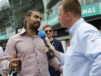 Former proffesional boxer David Haye of Britain talks to the media in the pit lane of the Sepang International Circuit outside Kuala Lumpur ahead of the Malaysian F1 Grand Prix March 25, 2012. REUTERS/Edgar Su