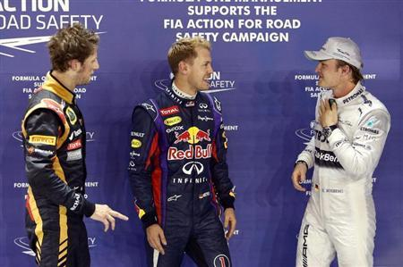 Lotus F1 Formula One driver Romain Grosjean of France (L), Red Bull Formula One driver Sebastian Vettel of Germany (C) and Mercedes Formula One driver Nico Rosberg of Germany (R) stand together after the qualifying session of the Singapore F1 Grand Prix at the Marina Bay street circuit in Singapore September 21, 2013. REUTERS/Tim Chong