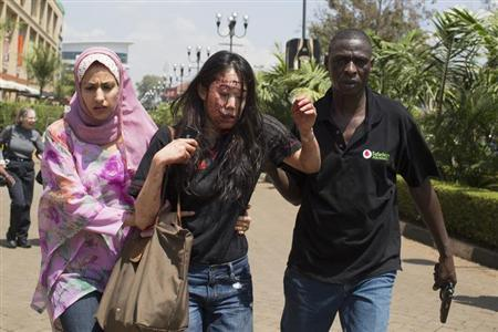 An injured woman (C) is helped out of the Westgate Shopping Centre where gunmen went on a shooting spree, in Nairobi September 21, 2013. The gunmen stormed the shopping mall in Nairobi on Saturday killing at least 20 people in what Kenya's government said could be a terrorist attack, and sending scores fleeing into shops, a cinema and onto the streets in search of safety. Sporadic gun shots could be heard hours after the assault started as soldiers surrounded the mall and police and soldiers combed the building, hunting down the attackers shop by shop. REUTERS/Siegfried Modola