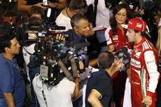 Ferrari Formula One driver Fernando Alonso of Spain is interviewed after the qualifying session of the Singapore F1 Grand Prix at the Marina Bay street circuit in Singapore September 21, 2013. REUTERS/Tim Chong
