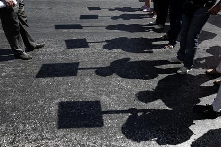 Protesters holding banners cast their shadows as they march during an anti-government rally in front of the parliament in Athens September 18, 2013. REUTERS/Yorgos Karahalis