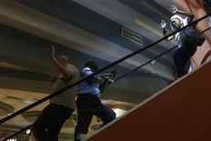 A police officer (C) secures an area as civilians flee inside Westgate Shopping Centre in Nairobi September 21, 2013. REUTERS/Siegfried Modola
