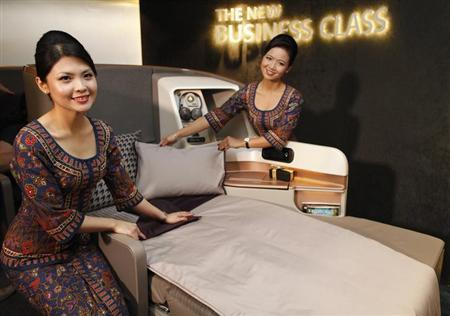 Singapore Airlines Ltd stewardesses pose next to a business class seat at Changi Airport in Singapore July 9, 2013. REUTERS/Edgar Su/Files