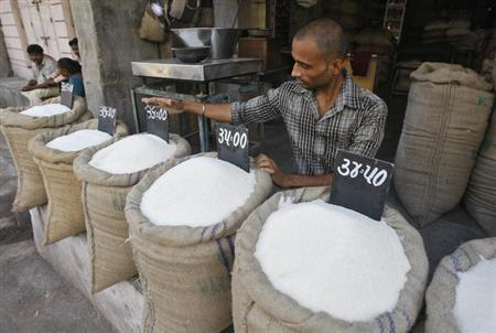 A vendor arranges a price tag over a sack filled with sugar at a wholesale vegetable market in Ahmedabad September 11, 2013. REUTERS/Amit Dave