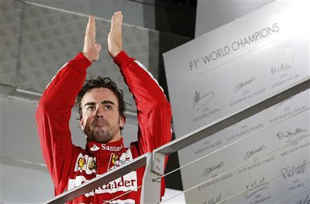 Ferrari Formula One driver Fernando Alonso of Spain claps on the podium after the Singapore F1 Grand Prix at the Marina Bay street circuit in Singapore September 22, 2013. REUTERS/Natashia Lee