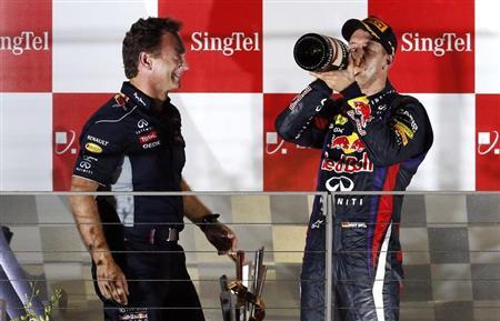Red Bull team principal Christian Horner (L) stands on the podium with Red Bull Formula One driver Sebastian Vettel of Germany after Vettel won the Singapore F1 Grand Prix at the Marina Bay street circuit in Singapore September 22, 2013. REUTERS/Edgar Su
