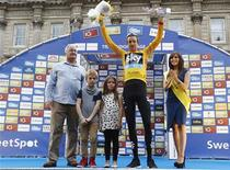 Britain's Bradley Wiggins (2nd R), with his children Ben and Isabella, celebrate being the overall winner of the Tour of Britain and receiving the gold jersey in Whitehall, central London September 22, 2013. REUTERS/Olivia Harris (BRITAIN - Tags: SPORT CYCLING) - RTX13V5T