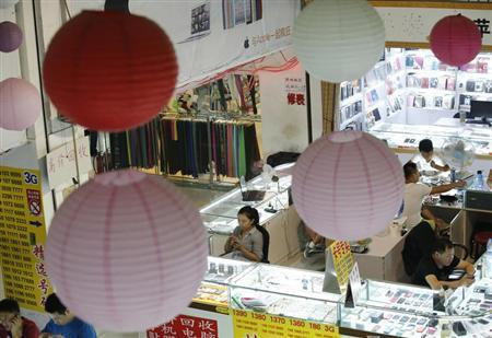 Sales people wait for customers at booths selling mobile phones in Beijing September 3, 2013. REUTERS/Kim Kyung-Hoon