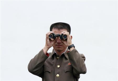 A North Korean soldier looks through a pair of binoculars while standing on a boat on the Yalu River, near the North Korean town of Sinuiju, opposite the Chinese border city of Dandong, September 21, 2013. REUTERS/Jacky Chen