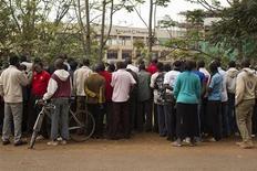Зеваки смотрят за происходящим в торговом центре Westgate в Найроби, где боевики удерживают заложников ходе схватки, унесшей десятки жизней 22 сентября 2013 года. Мощные взрывы и звуки стрельбы не прекращались в понедельник в торговом центре в столице Кении. REUTERS/Siegfried Modola