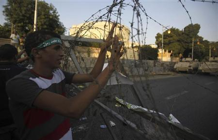 A member of the Muslim Brotherhood and supporter of ousted Egyptian President Mohamed Mursi holds onto barbed wire as he shouts slogans against the military and interior ministry near El-Thadiya presidential palace in Cairo September 20, 2013. REUTERS/Amr Abdallah Dalsh