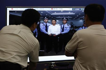 Men look at a screen displaying a picture of disgraced Chinese politician Bo Xilai standing trial on the website of a court's microblog, in Jinan, Shandong province September 22, 2013. REUTERS/Aly Song