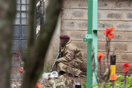 A security officer takes cover following a string of explosions from Westgate Shopping Centre in Nairobi during the third day of a stand-off between Kenyan security forces and gunmen inside the building September 23, 2013. REUTERS/Siegfried Modola