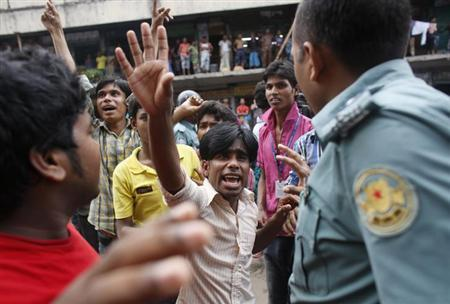 Garment workers urge a policeman to allow other workers to join in their protest, in Dhaka September 23, 2013. REUTERS/Andrew Biraj