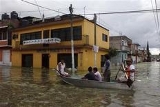 Unas personas sobre un bote en una calle inundada en Tixtla, México, sep 19 2013. Rescatistas buscaban el viernes en México a decenas de personas desaparecidas entre toneladas de lodo y casas destruidas, luego de los deslaves causados por las tormentas más destructivas que han golpeado al país en décadas. REUTERS/Stringer
