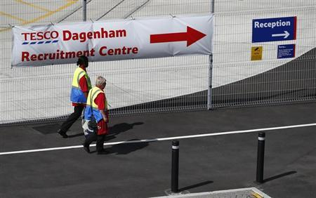 Workers pass a recruitment banner at Tesco's new distribution facility in Dagenham, east London August 12, 2013. REUTERS/Andrew Winning