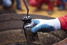 Un trabajador recolecta una muestra de crudo en un pozo de PDVSA en Morichal, Venezuela, jul 28 2011. La petrolera venezolana PDVSA lanzó una oferta para comprar 300.000 barriles de nafta catalítica para entrega entre el 6 y el 8 de octubre, dijo el lunes a Reuters una fuente cercana a la firma estatal. REUTERS/Carlos Garcia Rawlins