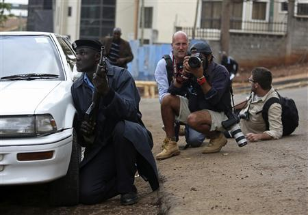 A policeman and photographers take cover after hearing gun shots near the Westgate shopping centre in Nairobi September 23, 2013. REUTERS/Karel Prinsloo