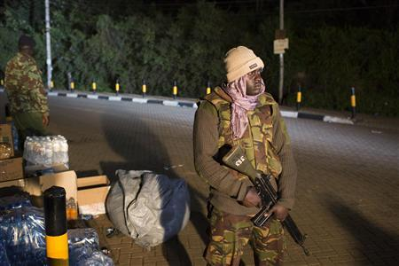 Police officers guard the edge of a security perimeter put into place a distance from the Westgate Shopping Centre in Nairobi, in the early hours of the morning during a standoff operation between Kenyan security forces and gunmen inside the building, September 24, 2013. REUTERS/Siegfried Modola
