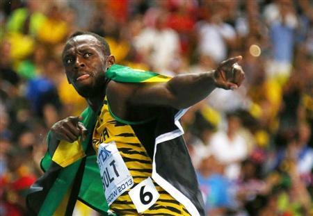 Usain Bolt of Jamaica poses with his national flag after winning the men's 100 metres final during the IAAF World Athletics Championships at the Luzhniki stadium in Moscow August 11, 2013. REUTERS/Kai Pfaffenbach