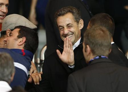 Former French President Nicolas Sarkozy waves as he arrives to attend the Paris St Germain and Monaco French Ligue 1 soccer match at the Parc des Princes Stadium in Paris September 22, 2013. REUTERS/Benoit Tessier