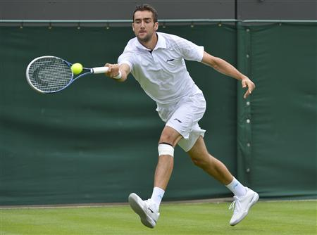 Marin Cilic of Croatia hits a return to Marcos Baghdatis of Cyprus in their men's singles tennis match at the Wimbledon Tennis Championships, in London June 24, 2013. REUTERS/Toby Melville