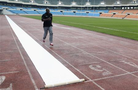 Sprinter Ben Johnson of Canada runs next to a scroll petition laid out on the track at the Seoul Olympic Stadium in Seoul September 24, 2013. REUTERS/Lee Jae-Won