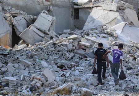 Boys walk amidst the rubble of damaged buildings in Duma neighbourhood of Damascus September 23, 2013. REUTERS/Bassam Khabieh