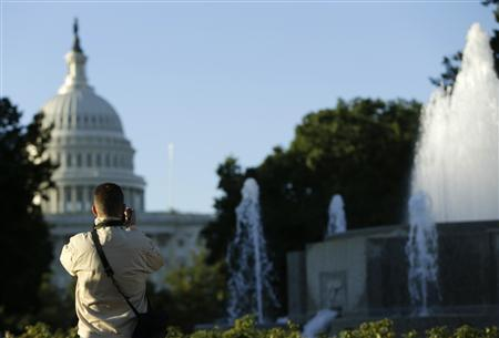 A man takes an early morning photograph of the U.S. Capitol dome near the Senate Garage Fountain in Washington September 24, 2013. REUTERS/Gary Cameron