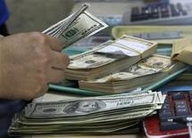 Un empleado cuenta dólares en una casa de cambio en Manila, sep 19 2013. El fracaso en elevar el límite de endeudamiento de Estados Unidos sería más nocivo para los mercados financieros que una paralización del Gobierno, señaló Moody's Investors Service. REUTERS/Romeo Ranoco