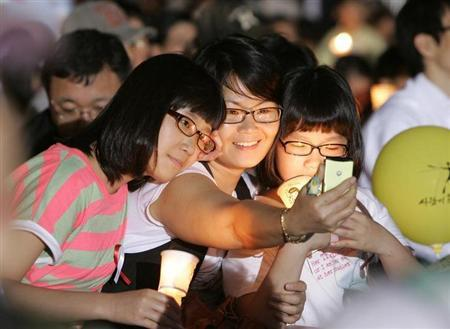 School girls take pictures of themselves using a mobile phone at the Seoul City Hall Plaza June 14, 2008. REUTERS/Jo Yong-Hak/Files