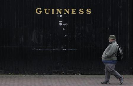 A man passes the Guinness beer factory in the city centre of Dublin December 6, 2011. REUTERS/Cathal McNaughton