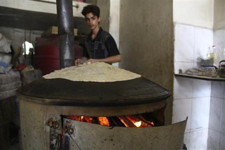 A man watches as bread is being baked in Duma neighbourhood, in Damascus September 22, 2013. REUTERS/Bassam Khabieh