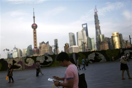 A man checks his iPad on the Bund in front of the financial district in Shanghai September 24, 2013. REUTERS/Aly Song
