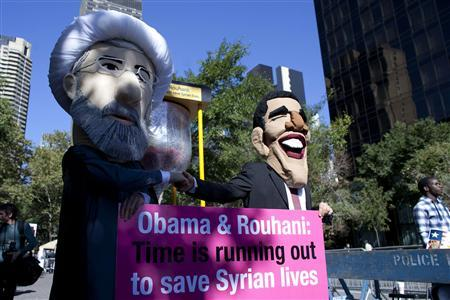 Members of international advocacy group Avaaz take part in a protest wearing masks of Iran's new President Hassan Rouhani (L) and U.S. president Barack Obama, outside the U.N. headquarters in New York September 24, 2013. REUTERS/Eduardo Munoz