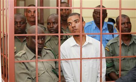 Jermaine John Grant (C, in white), a British citizen, is guarded by Kenyan police in court in Shanzu, near the Kenyan coastal city of Mombasa September 24, 2013. REUTERS/Joseph Okanga