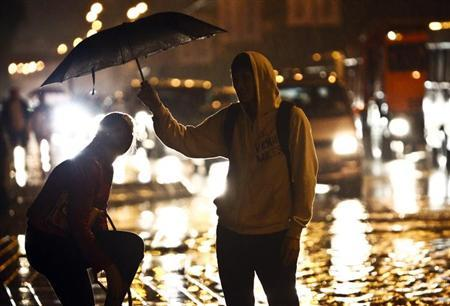A couple shelter under an umbrella as it rains in Sochi, September 24, 2013. REUTERS/Maxim Shemetov