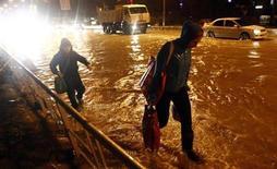 Pessoas caminham em rua alagada de Sochi, na Rússia. Autoridades regionais declararam estado de emergência em Sochi e isolaram uma localidade devido a inundações e deslizamentos de terra, menos de cinco meses antes de a cidade russa receber os Jogos Olímpicos de Inverno. 24/09/2013. REUTERS/Maxim Shemetov