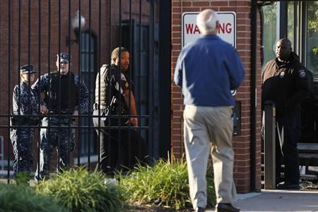 A Navy Yard personnel approaches a security checkpoint as he returns to work two days after a gunman killed 12 people before police shot him dead, in Washington, September 18, 2013. REUTERS/Jonathan Ernst