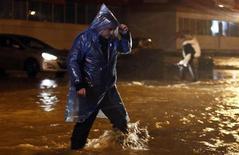 Мужчина пытается пройти по затопленной улице в Сочи 24 сентября 2013 года. Сильные даже для субтропического климата проливные дожди затопили будущую столицу зимней Олимпиады-2014 Сочи, вызвав оползни и вынудив жителей нескольких населенных пунктов покинуть свои дома, но ситуация начинает стабилизироваться, сообщили местные власти и МЧС. REUTERS/Maxim Shemetov