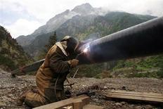 Рабочий чинит трубопровод в горах у поселка Бурон в Северной Осетии 17 июня 2009 года. Газпром и Транснефть могут увеличить в полтора раза закупки труб большого диаметра для магистральных газопроводов в следующем году после падения заказов на треть в этом году из-за переноса проектов Сила Сибири и Южный Поток, сказал в интервью Рейтер владелец трейдера Трубные инновационные технологии Иван Шабалов. REUTERS/Eduard Korniyenko