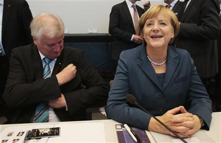 Bavarian state Premier Horst Seehofer and German Chancellor Angela Merkel await the start of a parliamentary group meeting of the Chirstian Democratic Union (CDU) and Christian Social Union (CSU) in Berlin September 24, 2013. REUTERS/Tobias Schwarz