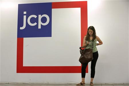 A woman checks her phone outside the entrance of a J.C. Penney store in New York in this file photo August 14, 2013. REUTERS/Brendan McDermid/Files