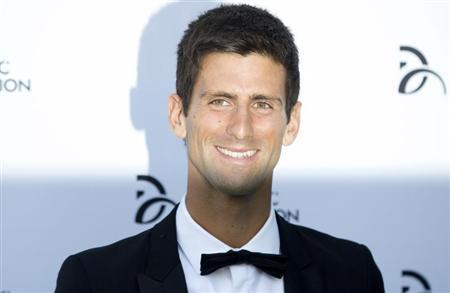 Serbian tennis player Novak Djokovic poses for photographers as he arrives at a fundraising dinner for the Novak Djokovic Foundation in London July 8, 2013. REUTERS/Neil Hall