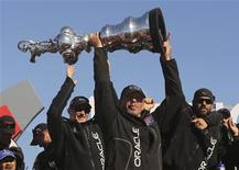 Oracle CEO Larry Ellison lifts the America's Cup with members of the Oracle Team USA after winning the overall title of the 34th America's Cup yacht sailing race over Emirates Team New Zealand in San Francisco, California September 25, 2013. REUTERS/Robert Galbraith