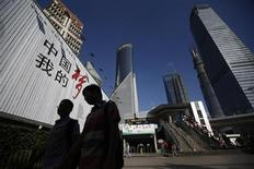 People walk past a billboard at the financial district of Pudong in Shanghai September 2, 2013. REUTERS/Aly Song