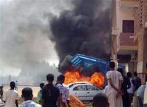 Un grupo de personas observa una serie de vehículos en llamas durante una serie de protestas por recortes a subsidios de combustibles en Jartum, sep 25 2013. Al menos 27 personas murieron durante las manifestaciones que se registraron en la capital de Sudán en protesta por los recortes a los subsidios del combustible, dijo el jueves una fuente médica, en la peor ola de violencia vista en años en la región central del país. REUTERS/Stringer