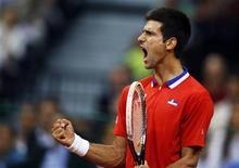 El número uno del tenis mundial, el serbio Novak Djokovic, celebra tras ganar un punto frente al canadiense Milos Raonic en su encuentro por Copa Davis en Belgrado, sep 15 2013. Djokovic anunció a través de las redes sociales que se comprometió con su novia, Jelena Ristic. REUTERS/Marko Djurica