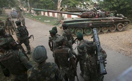A tank from the Indian army moves past soldiers during a search operation after a gun battle at an army camp in Mesar in Samba district September 26, 2013. REUTERS/Mukesh Gupta
