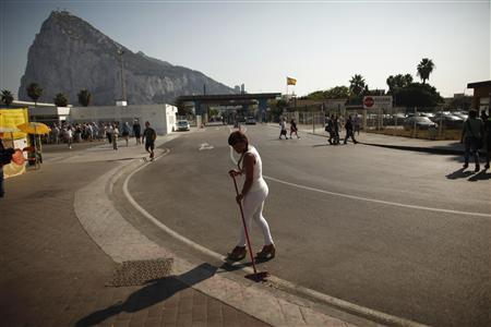 A woman sweeps the floor next to the entrance of the border of Spain (rear) with the British territory of Gibraltar before the arrival of European Commission officials (not pictured) to check the border in La Linea de la Concepcion, southern Spain September 25, 2013. REUTERS/Jon Nazca